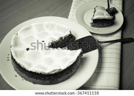 Sweet cake with chocolate on a light wooden table. Toned.