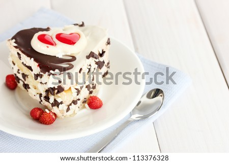 sweet cake with chocolate on plate on wooden table