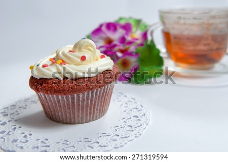 Sweet cake with cup of tea and flowers - stock photo