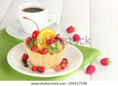 sweet cake with fruits on plate and cup of coffee on wooden table - stock photo