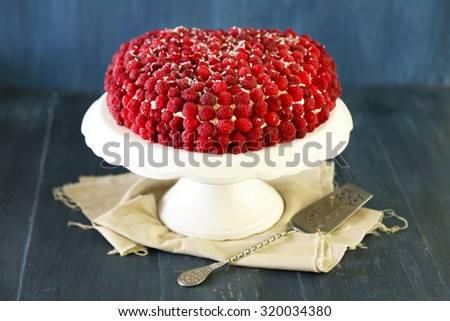Sweet cake with raspberries on color wooden background - stock photo