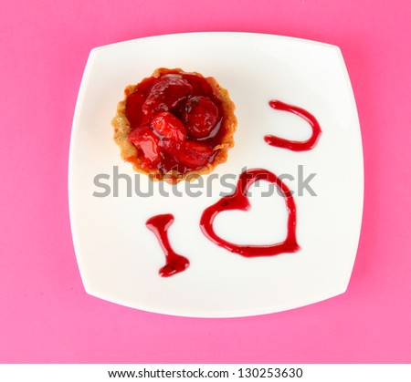 Sweet cake with strawberry and sauce on plate, on color background - stock photo