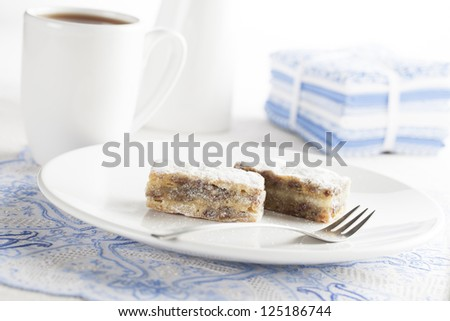 Sweet cakes with powdered sugar served with tea.