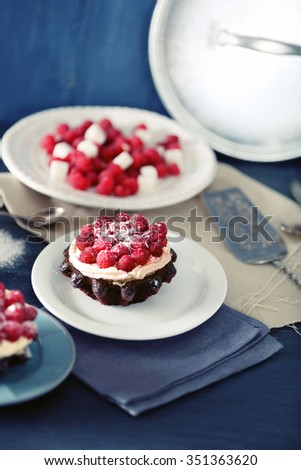 Sweet cakes with raspberries on color wooden background - stock photo