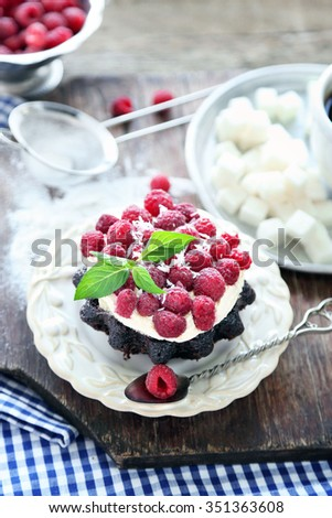 Sweet cakes with raspberries on wooden table background - stock photo