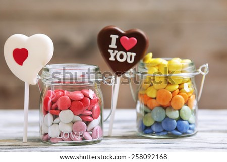 Sweet candies in glass jar with hearts on wooden background - stock photo