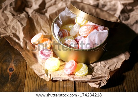 Sweet candies in metal can, on wooden background - stock photo