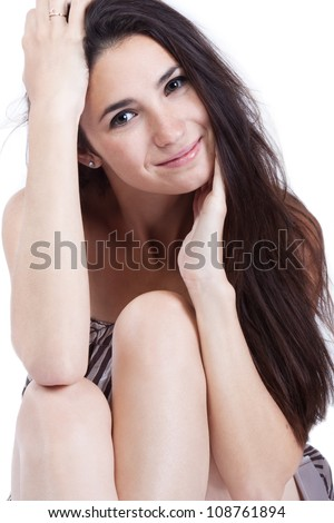 Sweet caucasian woman face with natural makeup and long hair smiling and looking tenderly into the camera. Female has a clean skin on arms and legs. Isolated white.