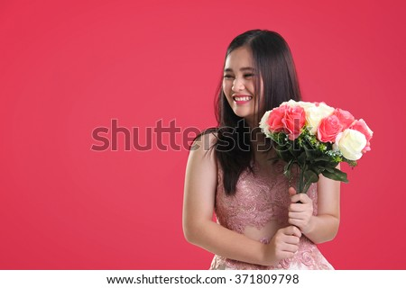 Sweet cheerful Asian teenage girl with natural smile holding a bouquet of roses, looking sideways at copy space on pink background for Valentines Day - stock photo