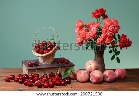 Sweet cherries, books and flowers in a vase on the table - stock photo