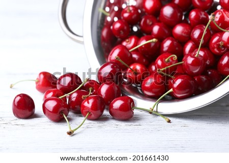 Sweet cherries in colander on color wooden background - stock photo