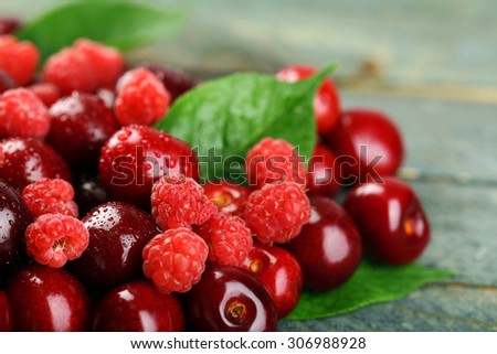 Sweet cherries, raspberries with green leaves on wooden background