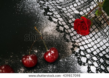 Sweet cherry against black background, lacy drawing from icing sugar and red rose - stock photo