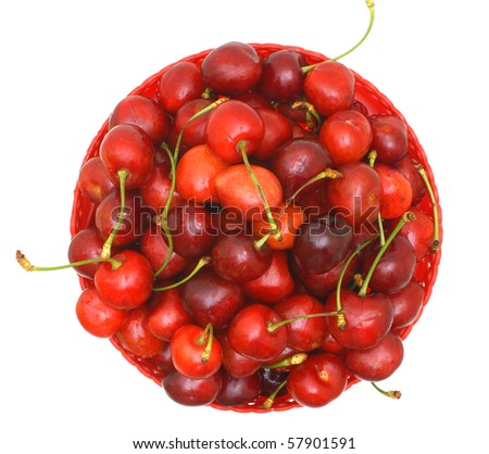 Sweet cherry fruits in a red plate from above on a white background.