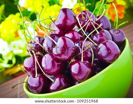 Sweet cherry fruits in colorful bowl - stock photo