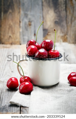 sweet cherry in the cup on wooden table