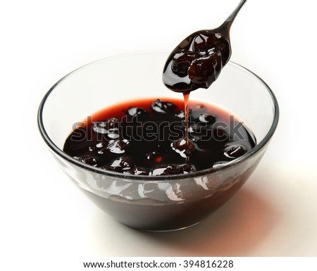 Sweet cherry jam in the transparent glass bowl and tea spoon on a white background - stock photo