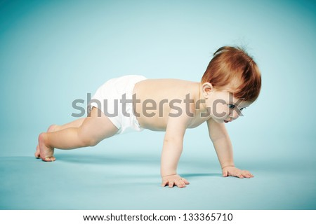 sweet child crawls on blue background - stock photo