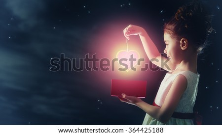 Sweet child girl with red heart. Happy little girl with gift box on background of star sky. Wedding, Valentine, celebration concept. - stock photo