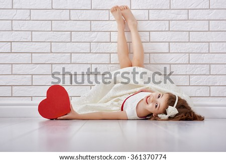 Sweet child girl with red heart. Happy little girl with Valentine's gift at a blank brick wall. Wedding, Valentine concept. - stock photo
