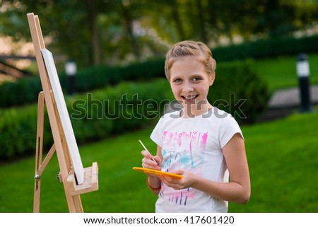 Sweet child is posing for the camera while drawing her new picture outdoors. Wise combination of a hobby and leisure time by spending time on nature. Lovely smile of a little girl. - stock photo