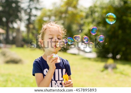 Sweet child playing with soap bubble
