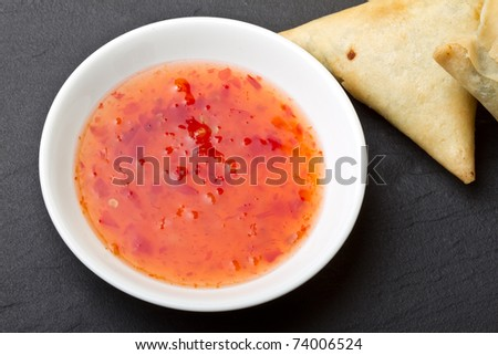 Sweet chilli dipping sauce and golden fried samosa's on dark slate background. - stock photo