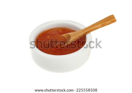 Sweet chilli dipping sauce in a ramekin with a wooden spoon isolated against white - stock photo