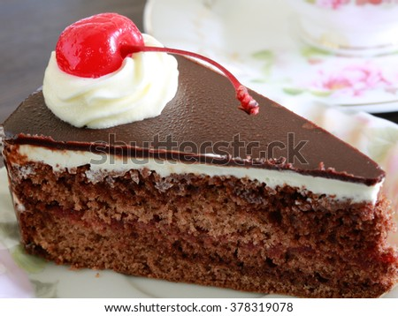 sweet choc cake with cup of tea on wooden table