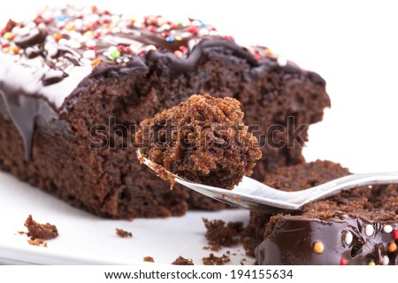 Sweet chocolate cake with colored candy on the top close-up isolated on white - stock photo