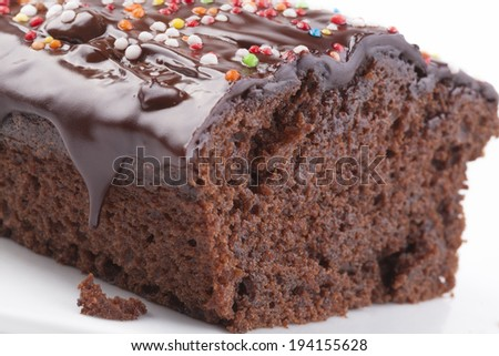 Sweet chocolate cake with colored candy on the top isolated on white - stock photo