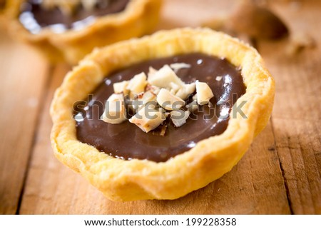 Sweet chocolate mini tart on the wooden table  - stock photo