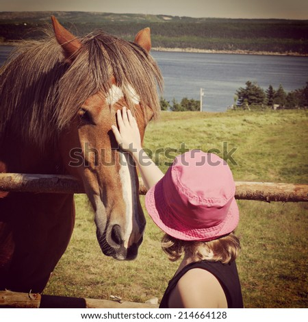 sweet closeup instagram of young girl petting horse - stock photo