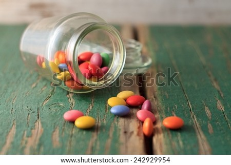 Sweet color chocolate smarties on wooden table with old worn green color and glass jar placed near the pile. - stock photo