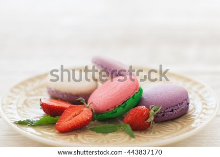 Sweet colorful macaroons with strawberry slices on plate copyspace. Front view on white glass plate with colorful macaroons served with fresh strawberry. Some free space - stock photo
