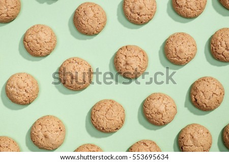 Sweet cookies flat lay pattern on light green background