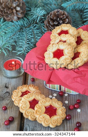 Sweet cookies with jam, fir branches and cones, cranberries and red burning candle on the old wooden table