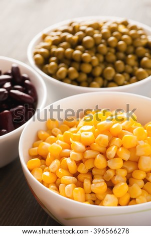 Sweet corn and green peas in white bowls closeup, selective focus, vertical - stock photo