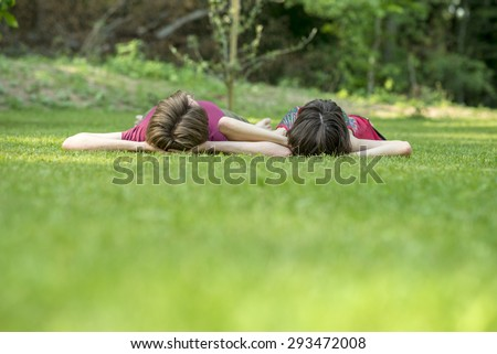Sweet Couple Lying on the Grassy Ground Outside with Both Hands on their Heads and Facing Up. - stock photo