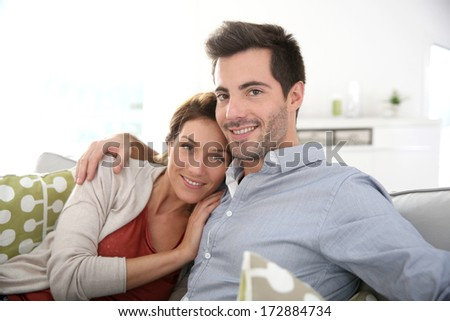 Sweet couple relaxing in sofa at home - stock photo
