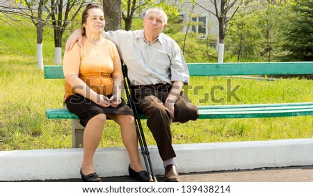 Sweet couple talking and sitting on the bench park - stock photo