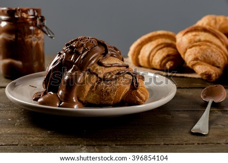 Sweet croissant with chocolate on rustic background - stock photo