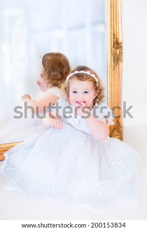 Sweet curly little girl with big beautiful eyes wearing a white bridesmaid dress sitting at a big window playing princess in a sunny living room - stock photo