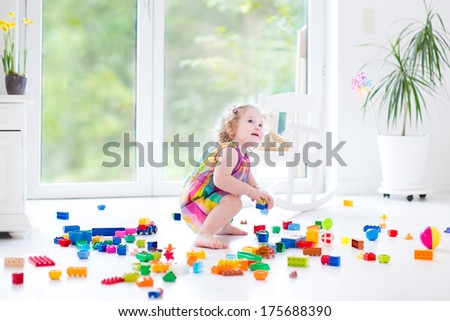Sweet curly toddler girl playing with colorful blocks sitting on a floor in a sunny bedroom with a big window - stock photo