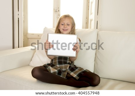 sweet cute and beautiful 6 or 7 years old female child with blond hair in school uniform sitting on home sofa couch using internet app holding digital tablet pad playing online game smiling happy - stock photo