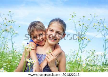 Sweet cute kids in a meadow with wild spring flowers