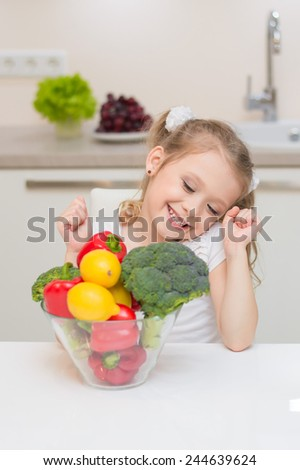 Sweet cute young girl with two ponytails smile and choose one of healthy ripe colorful vegetables and fruits for cooking.