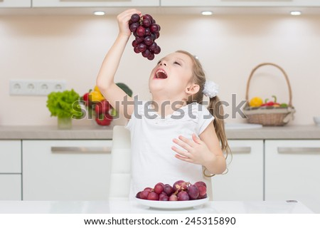 Sweet cute young girl with two ponytails smile and eat the fresh grapes. - stock photo