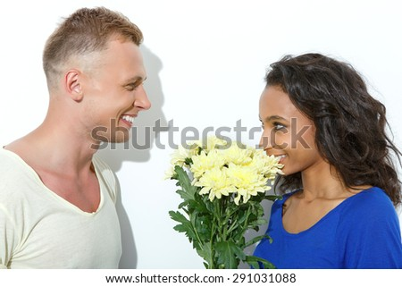 Sweet date. Portrait of a blond young man looking his beautiful mulatto girlfriend smelling a bunch of yellow flowers smiling, isolated on white background