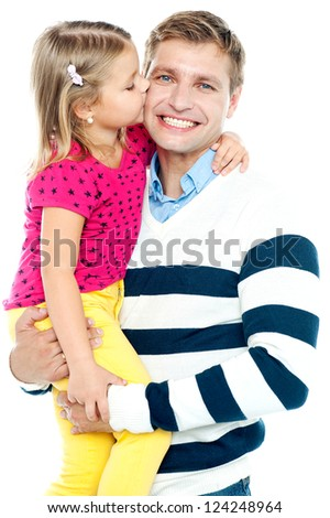 Sweet daughter kissing her smiling father while he holds her in his arms - stock photo